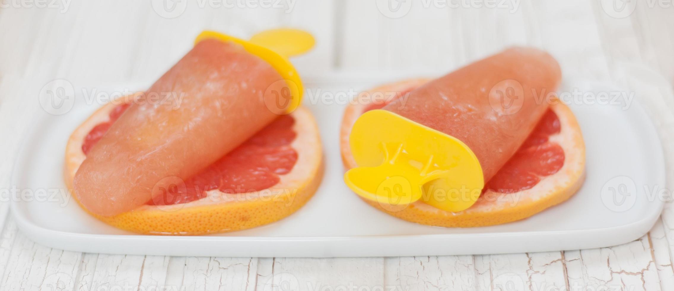 fruitige ijsjes geserveerd op schijfjes grapefruit foto