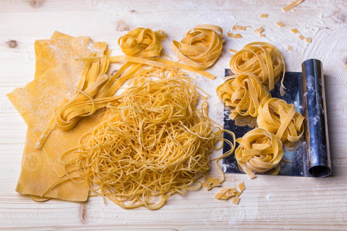 zelfgemaakte noedels en pasta op houten tafel foto