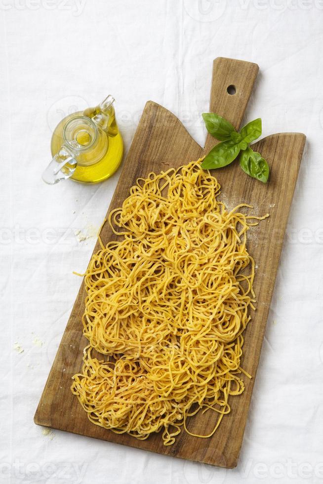 verse zelfgemaakte spaghetti op een snijplank foto