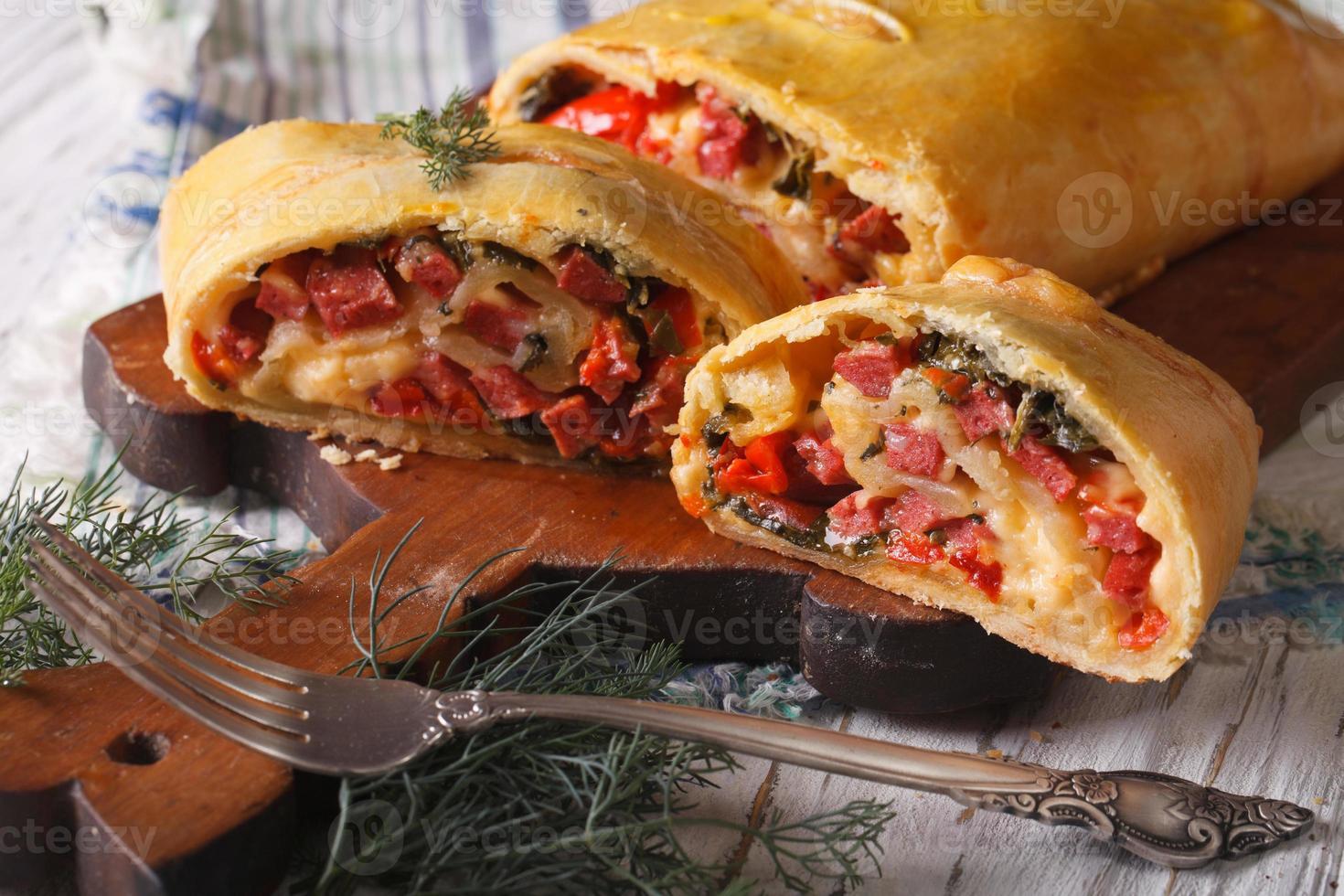 strudel met ham, kaas en groenten close-up. horizontaal foto