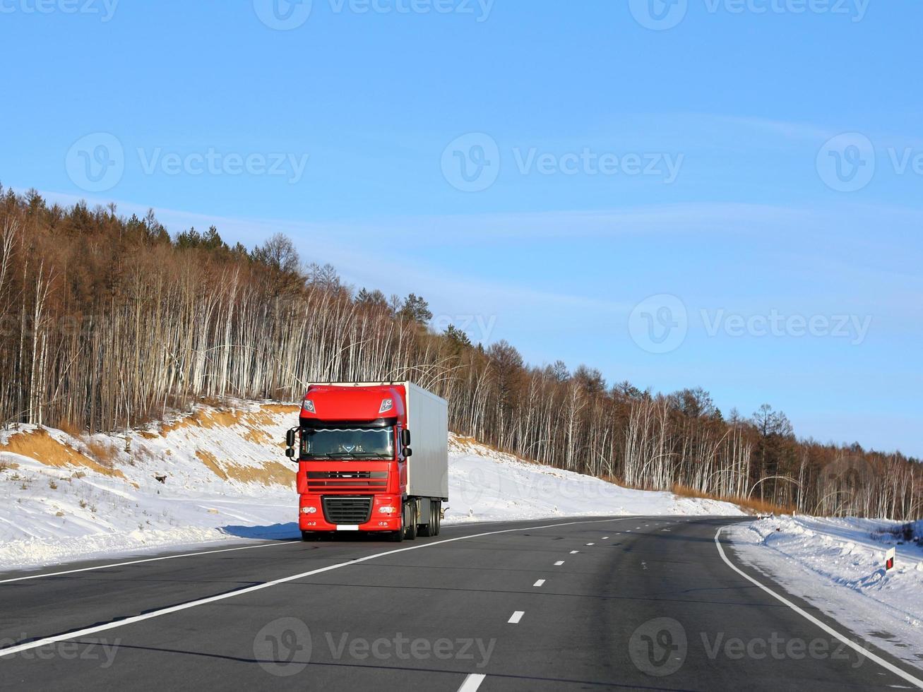 grote rode vrachtwagen op weg met sneeuw foto
