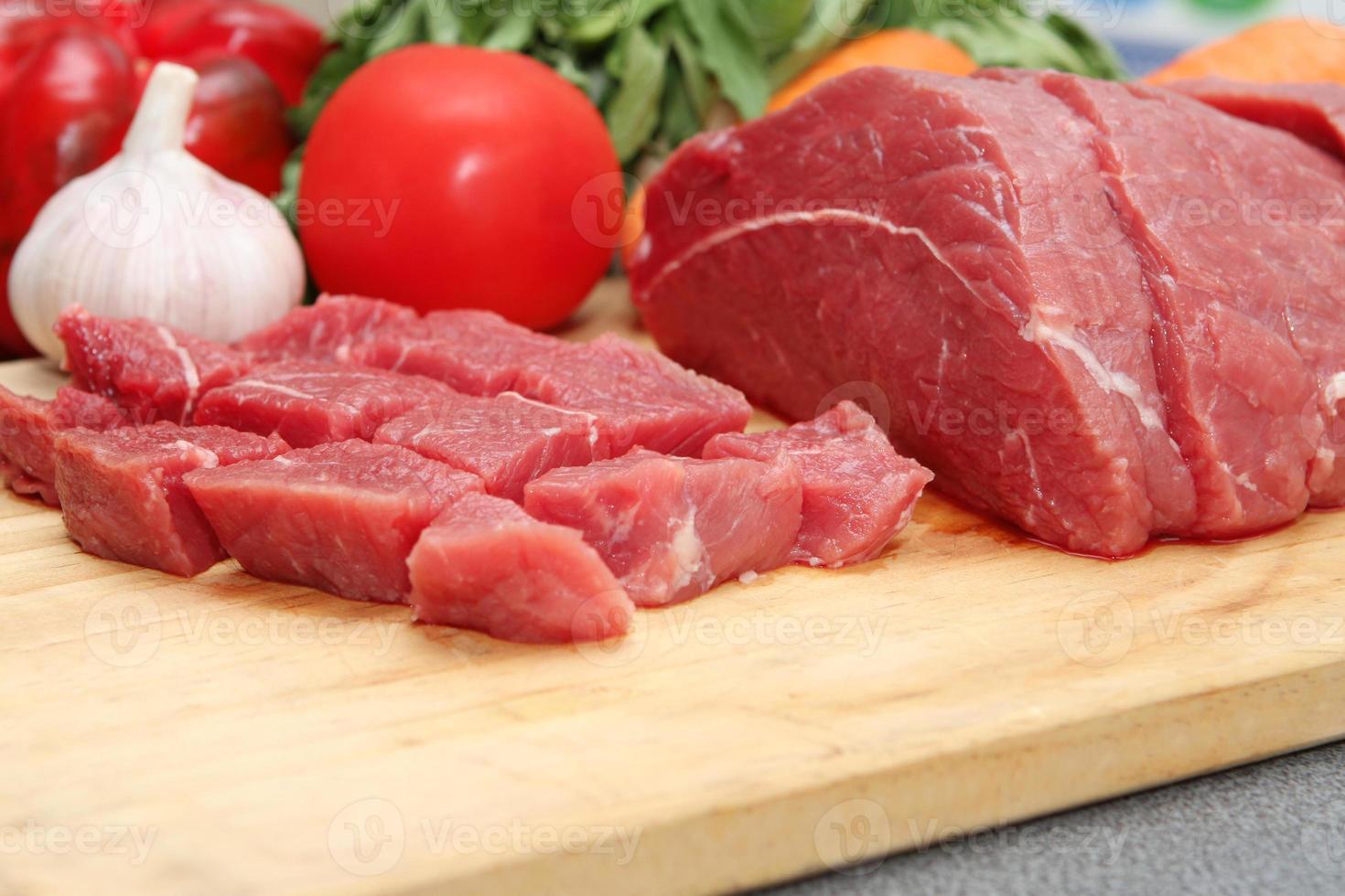 rauw rundvlees, tomaat en knoflook op houten plaat foto