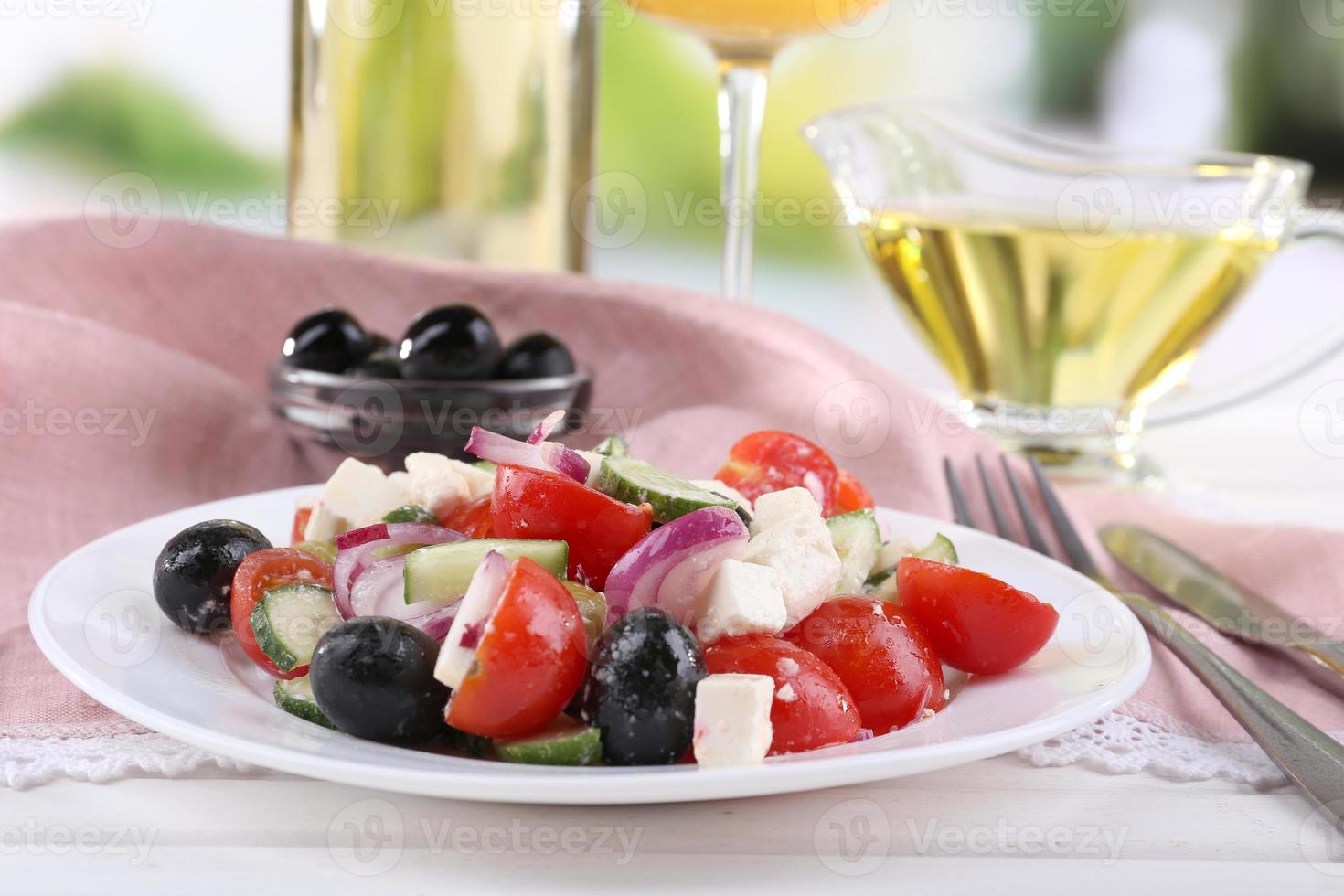 Griekse salade geserveerd in plaat met wijn op tafel foto