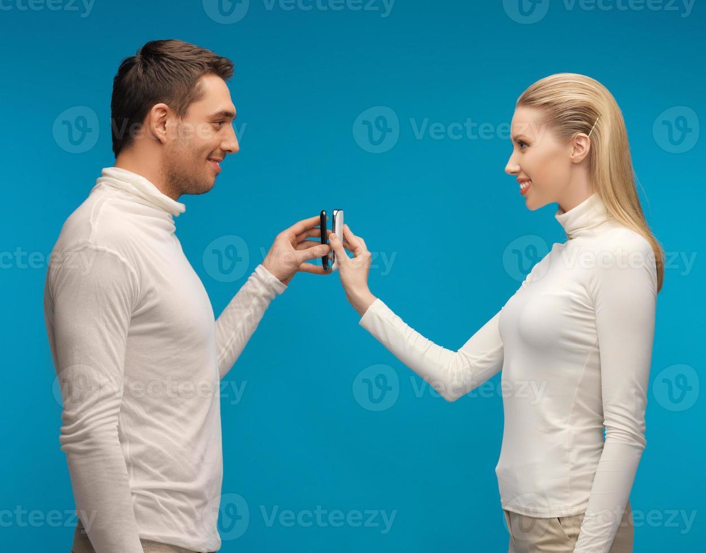 man en vrouw met smartphones foto