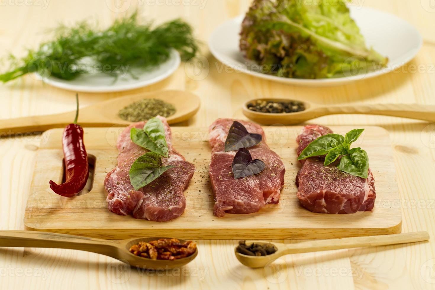verse rauwe varkensvlees op snijplank met specerijen en kruiden foto
