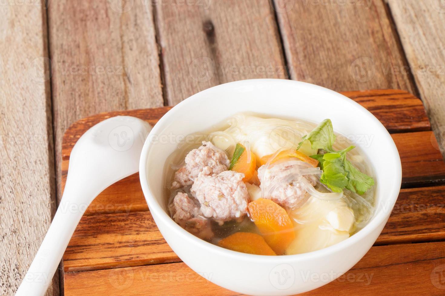 duidelijke soep met varkensvlees in witte plaat foto