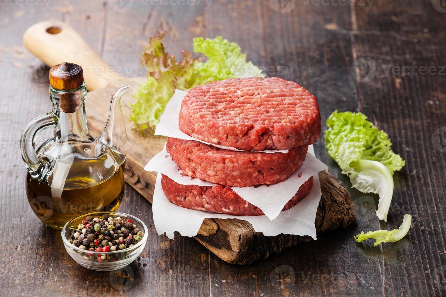 een stapel van rauwe rundvlees hamburgers op een snijplank foto