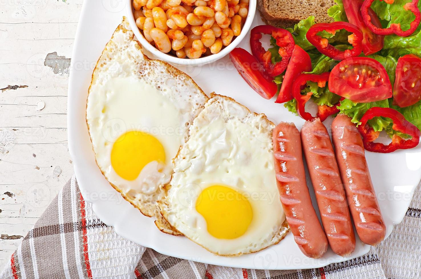 Engels ontbijt - worstjes, eieren, bonen en salade foto