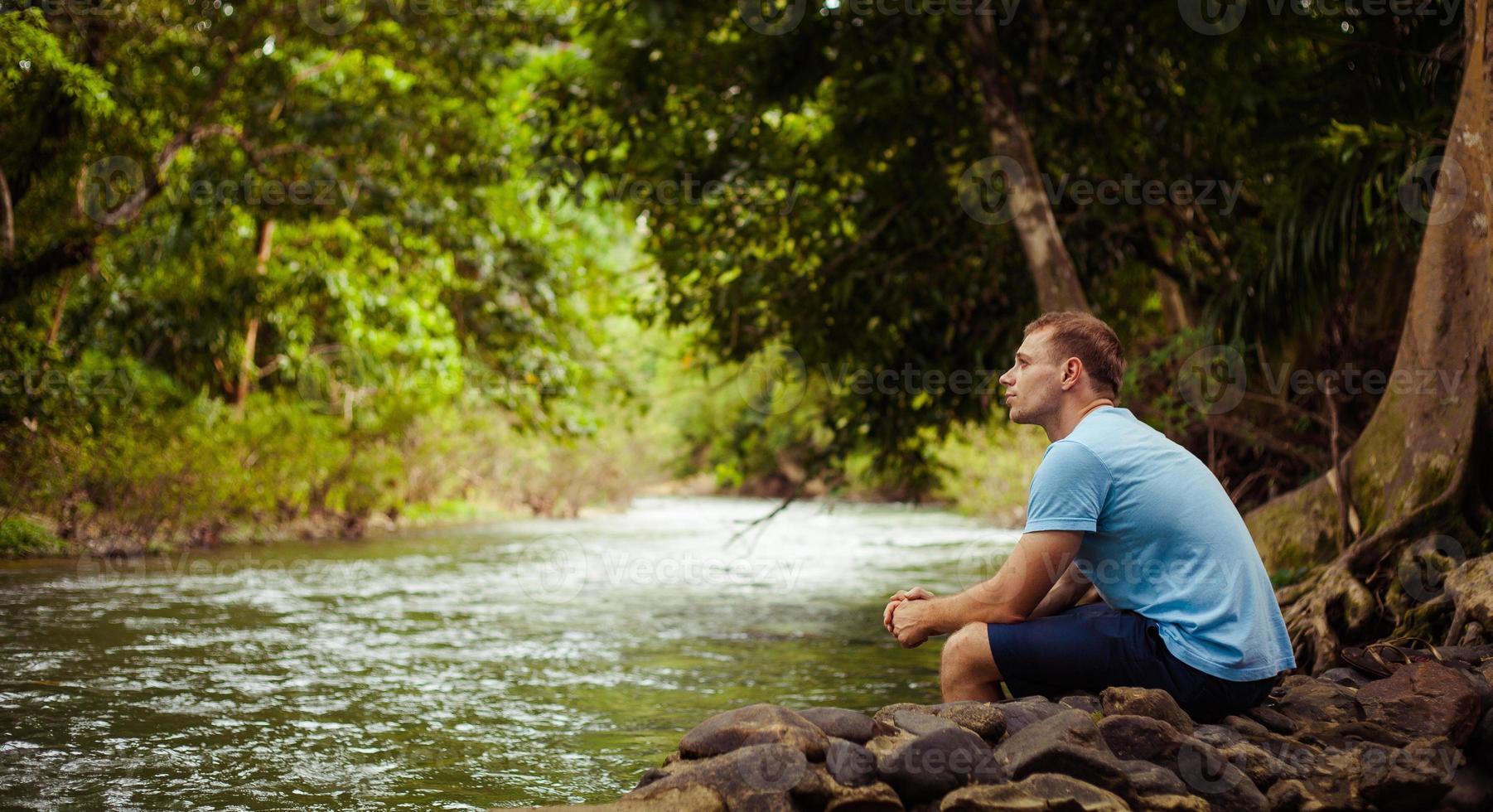 man zit door jungle rivier overweegt foto