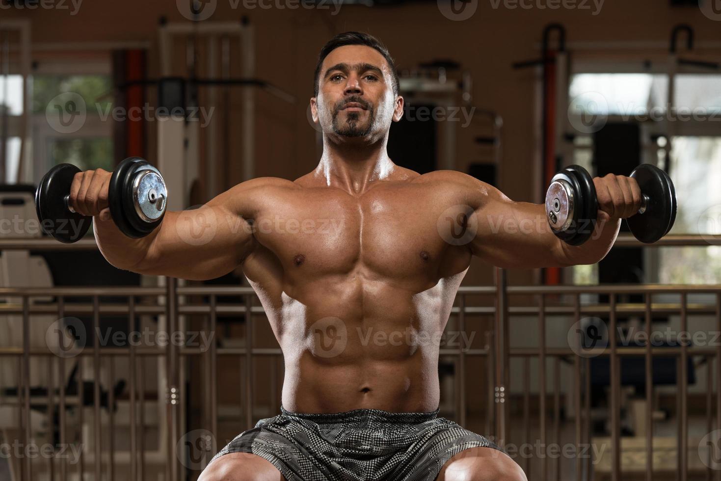 bodybuilder die zwaargewicht oefening voor schouders doet foto