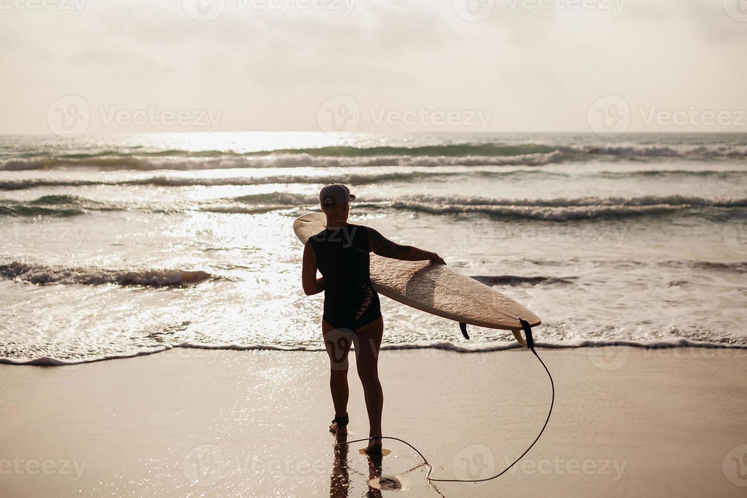 vrouw met surfplank achteraanzicht surfen foto