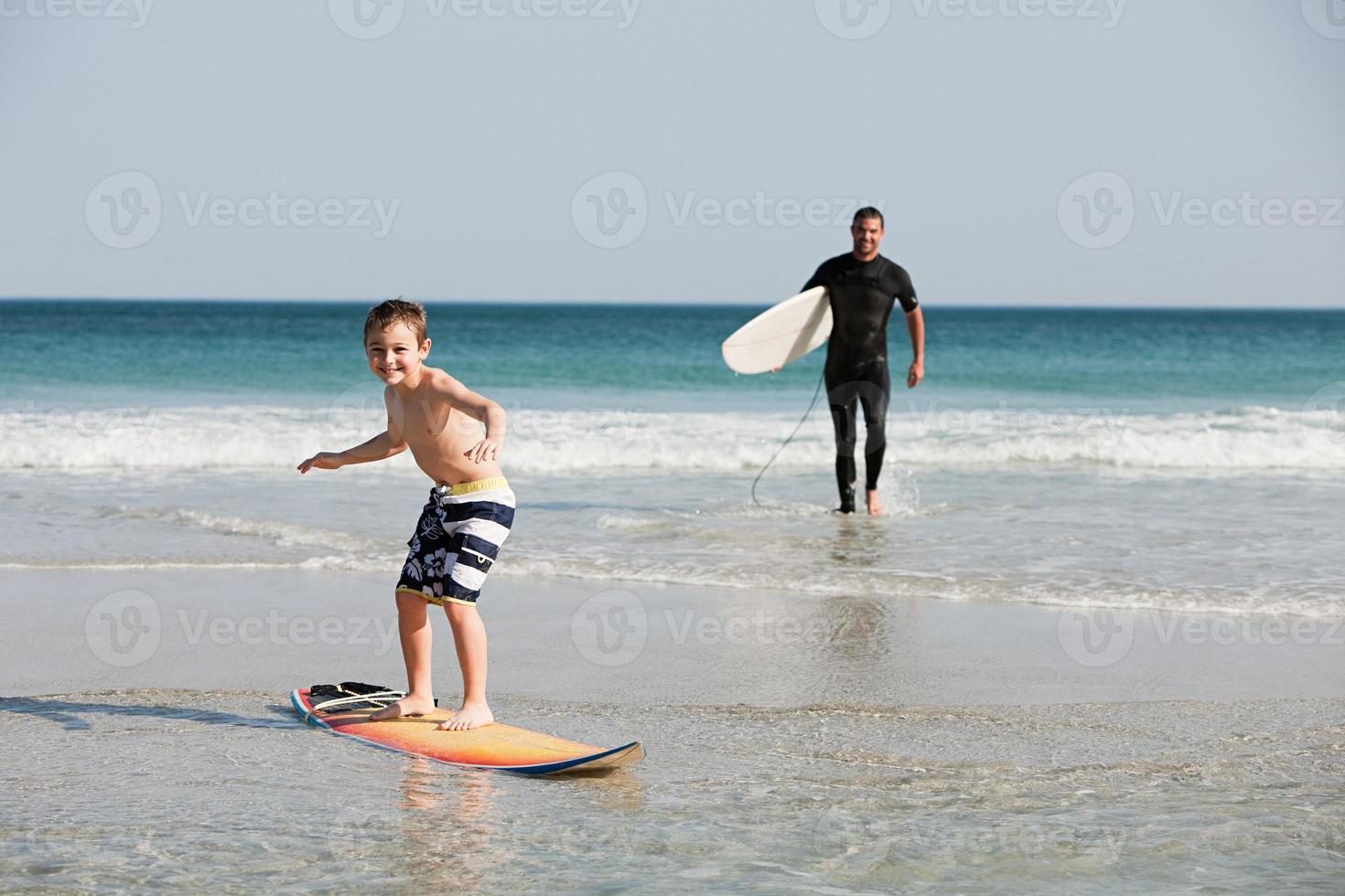 jongen surfen in ondiep water foto