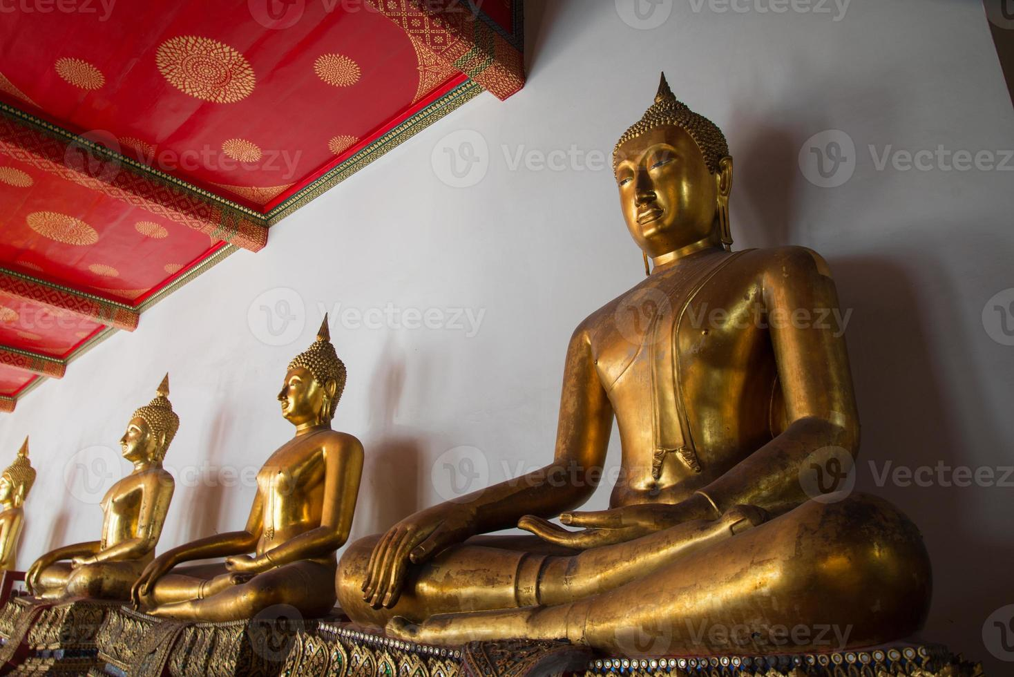 rij van boeddha's in tempel in bangkok foto