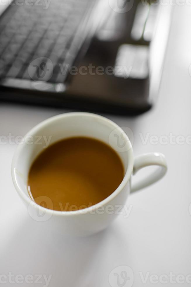 koffiekopje en laptop voor het bedrijfsleven, selectieve focus op koffie. foto