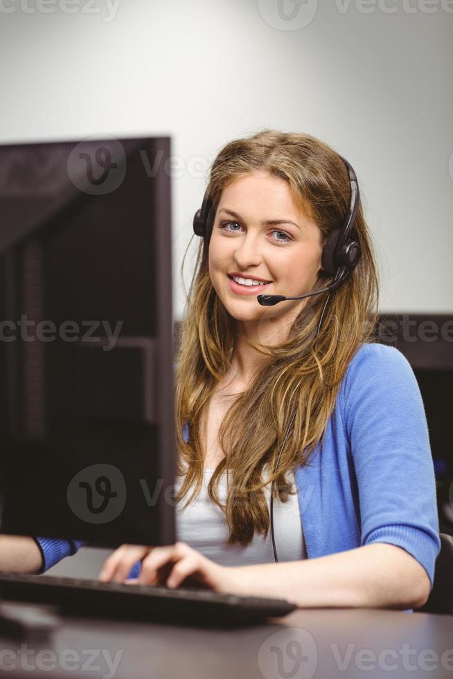 studentenzitting bij de computerzaal die hoofdtelefoon draagt foto