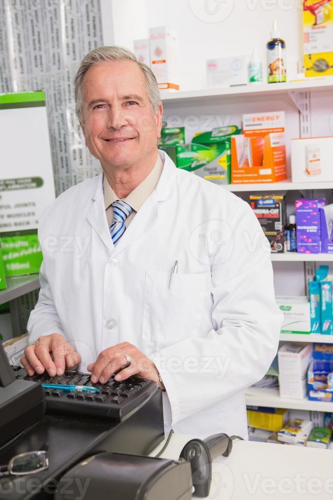 lachende senior apotheker met behulp van computer foto