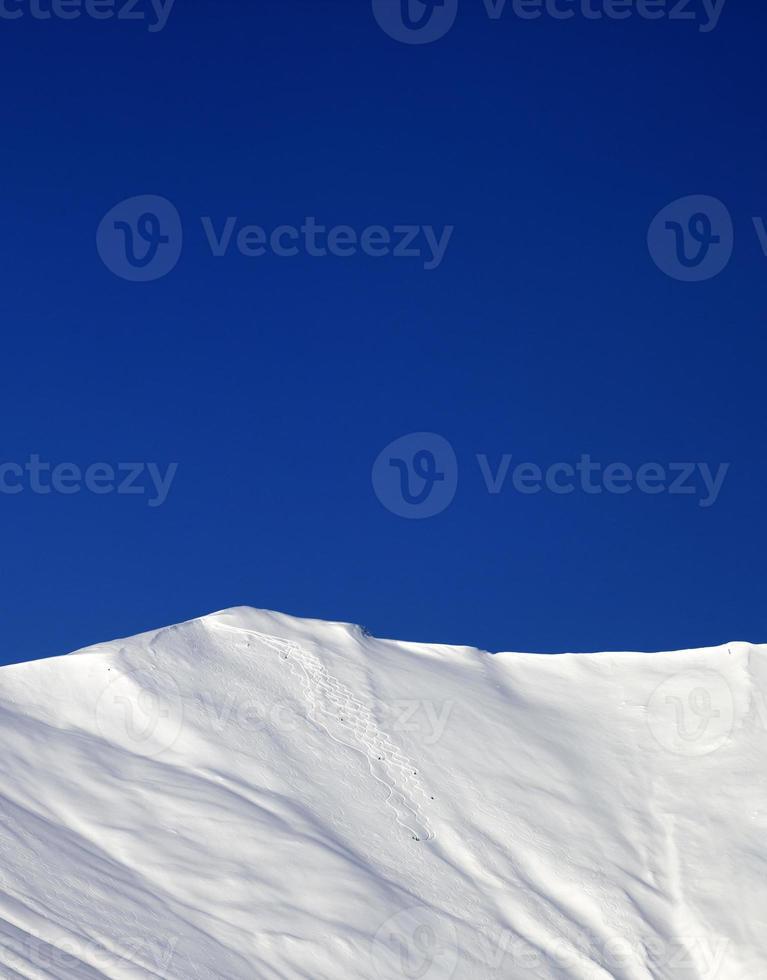 off-piste helling en blauwe heldere hemel in zon winterdag foto
