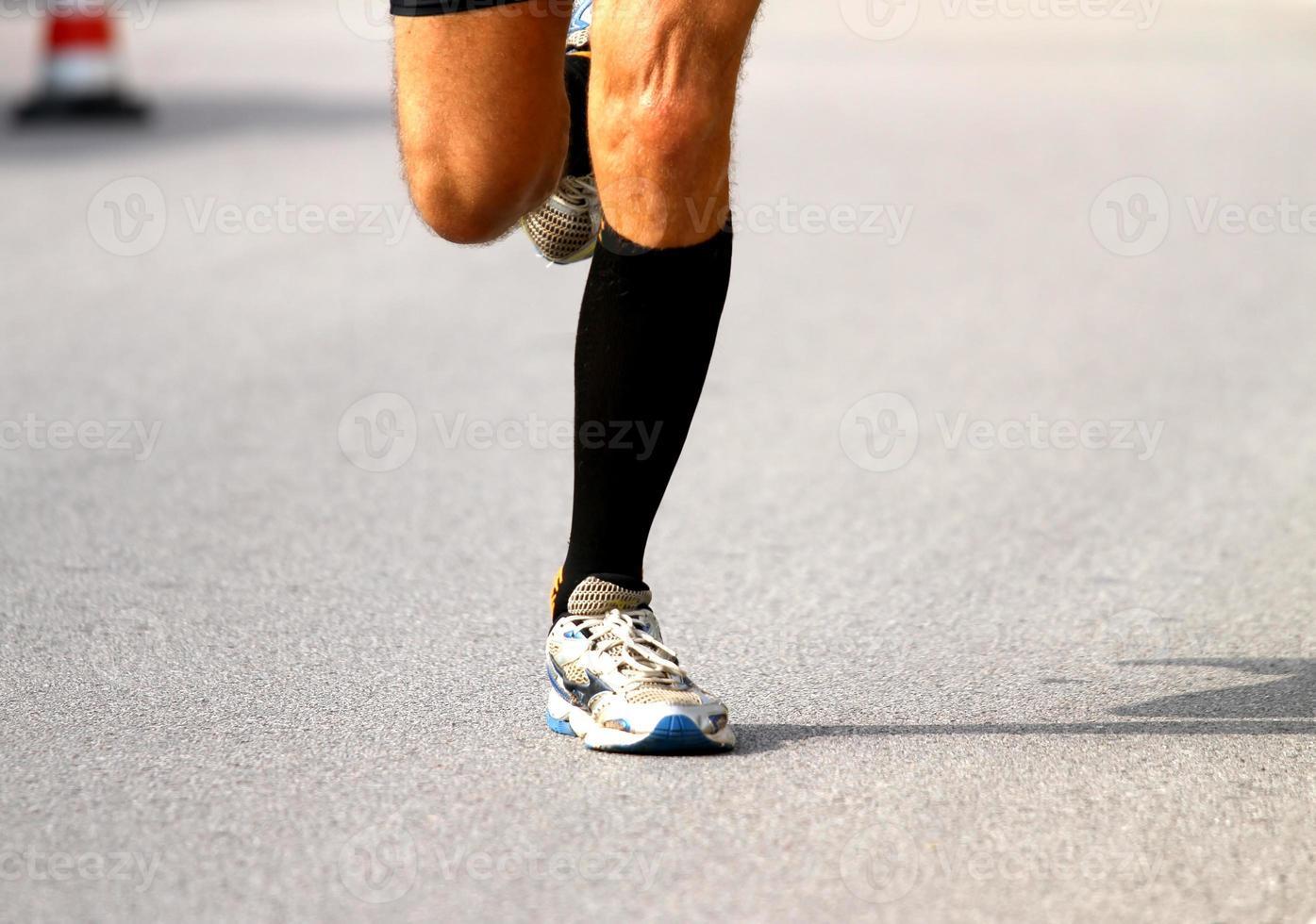 snelle loper met sneakers tijdens de marathon op de weg foto