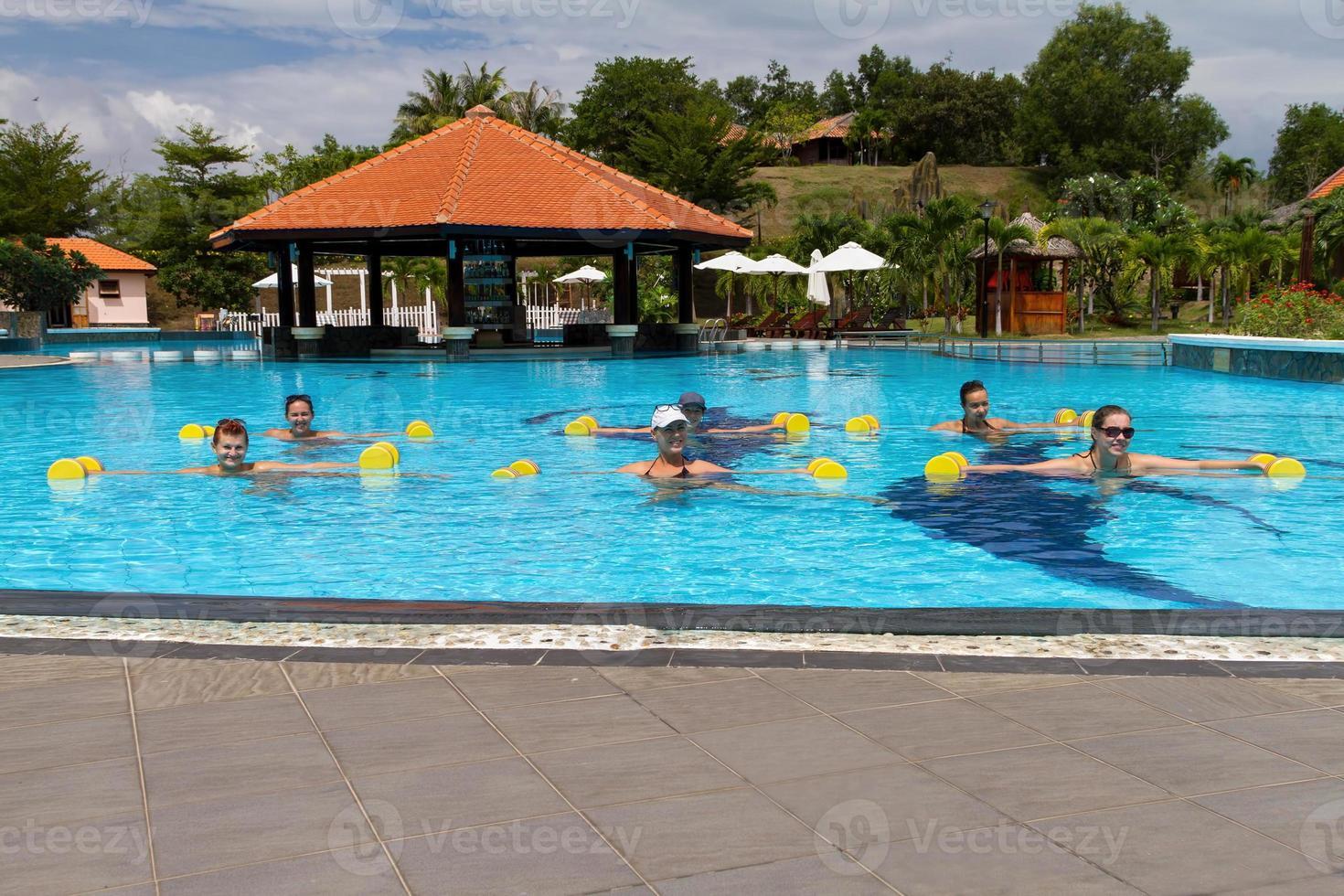 glimlachende groep die aqua-aerobics in zwembad met domoren doet foto