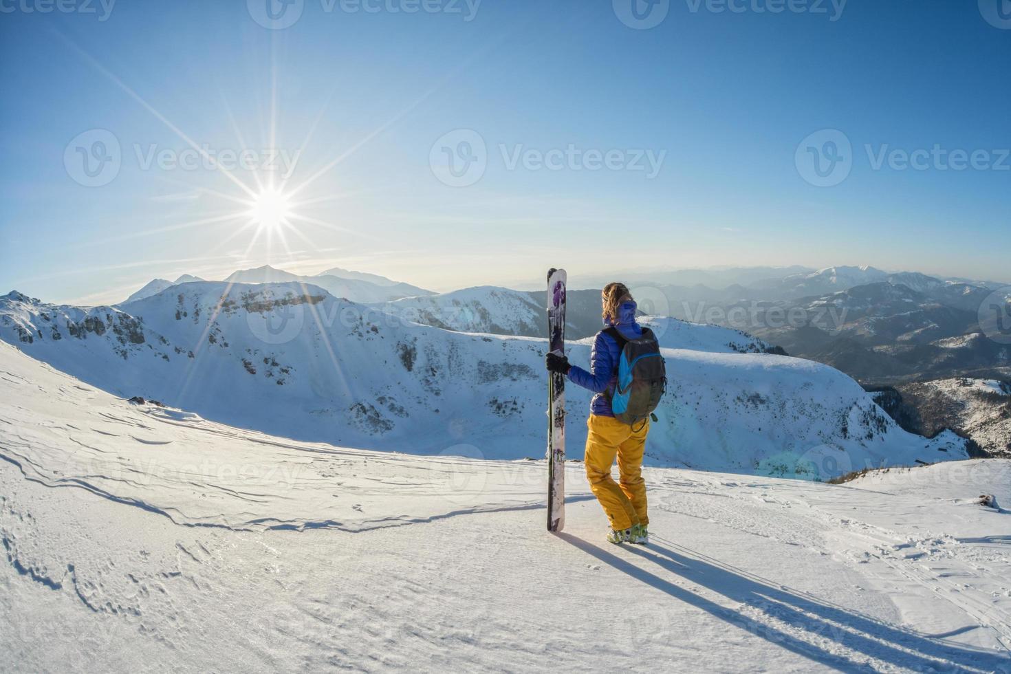 skiër overweegt zonsondergang uitzicht vanaf de top van besneeuwde berg foto