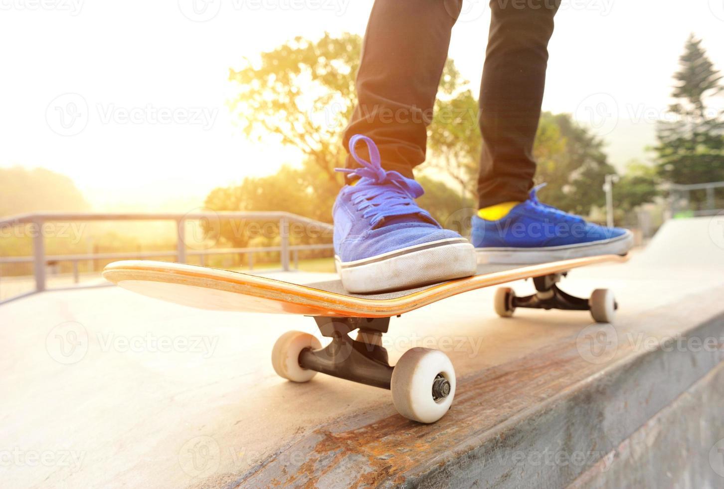 benen in sneakers op een skateboard foto