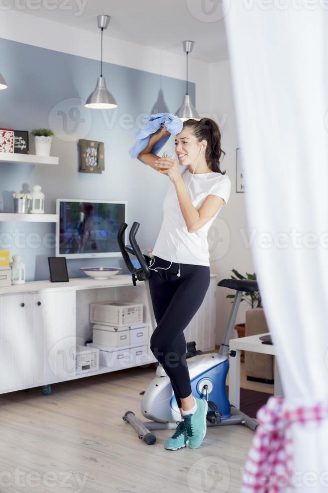 vrouw drinken tijdens het trainen op een hometrainer foto