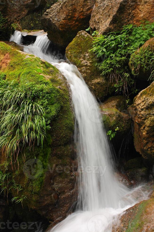 zuiver zoet water waterval loopt over bemoste rotsen foto