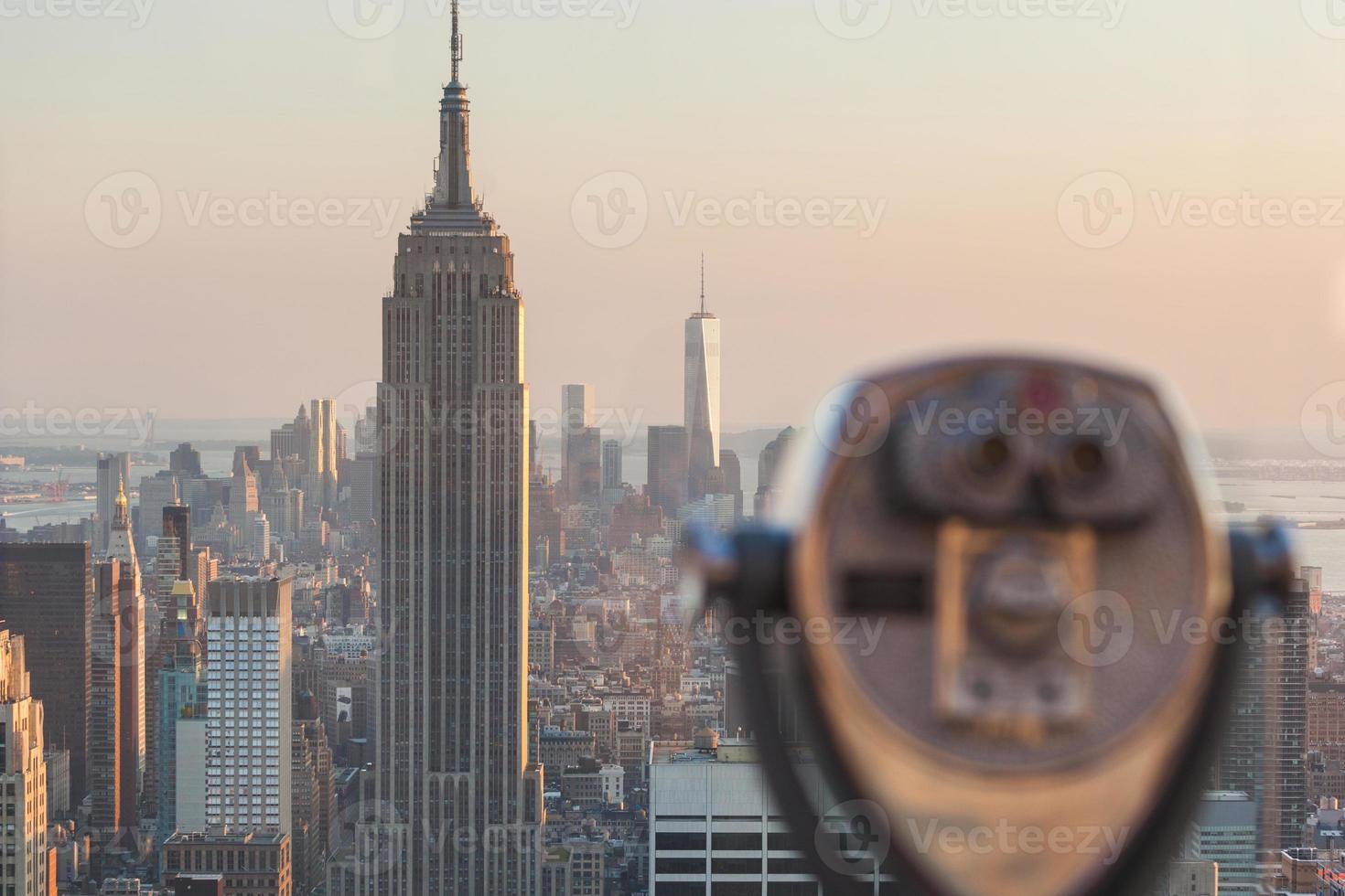 verrekijker met wolkenkrabbers van New York op de achtergrond bij zonsondergang foto