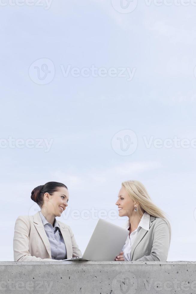 gelukkige jonge vrouwelijke ondernemers met laptop bespreken foto