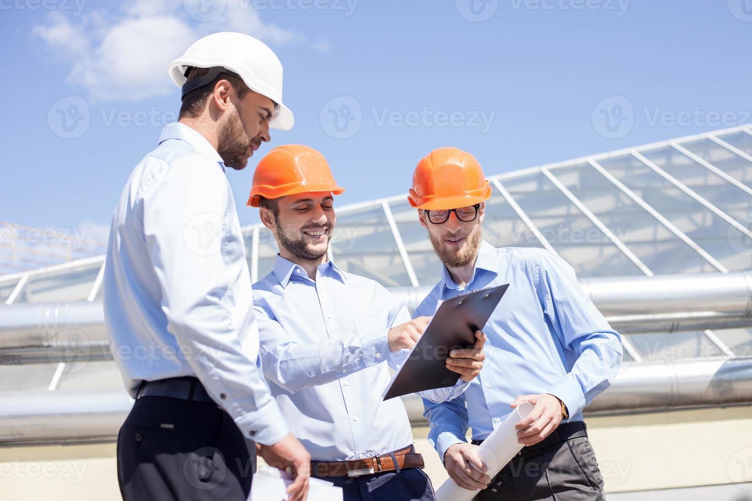 knappe jonge bouwers plannen het nieuwe project foto