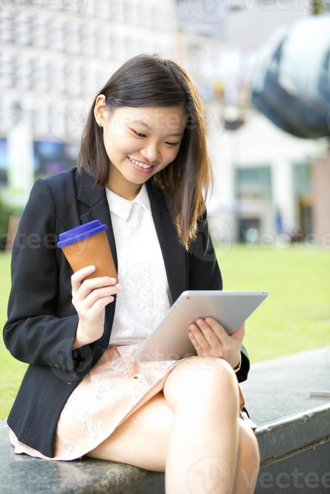 jonge vrouwelijke Aziatische zakenman met behulp van tablet foto