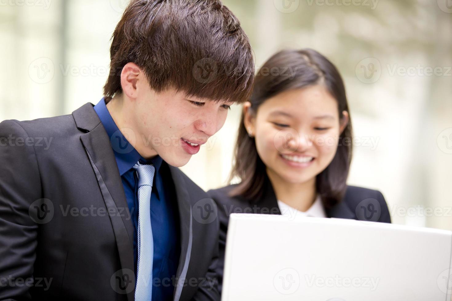 jonge vrouwelijke en mannelijke Aziatische directeur die laptop met behulp van foto
