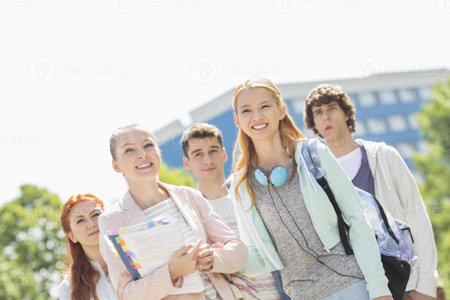 lachende jonge studenten staan samen op de campus van de universiteit foto