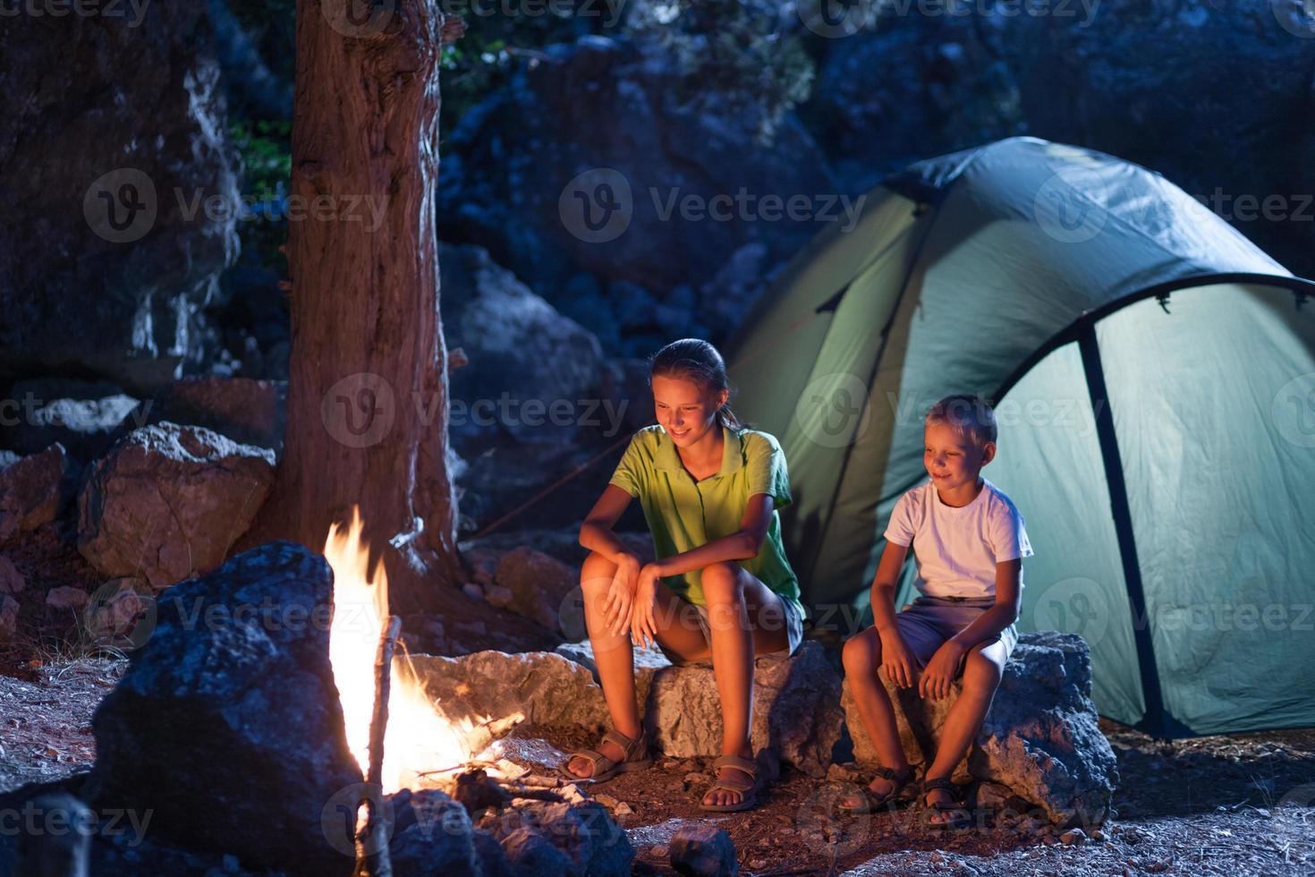 zus met broer bij het kampvuur foto