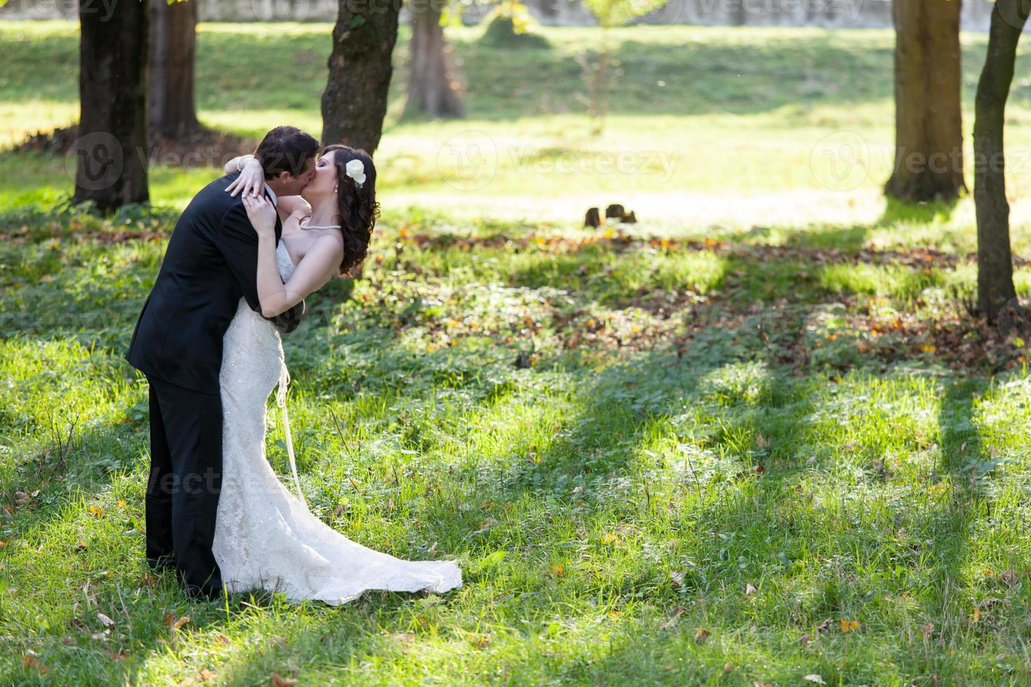 elegante bruid en bruidegom poseren samen buitenshuis foto