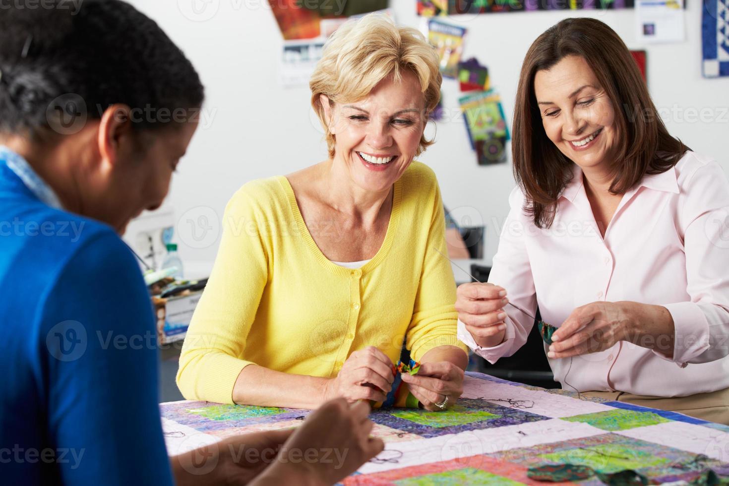 groep vrouwen die samen quilt maken foto