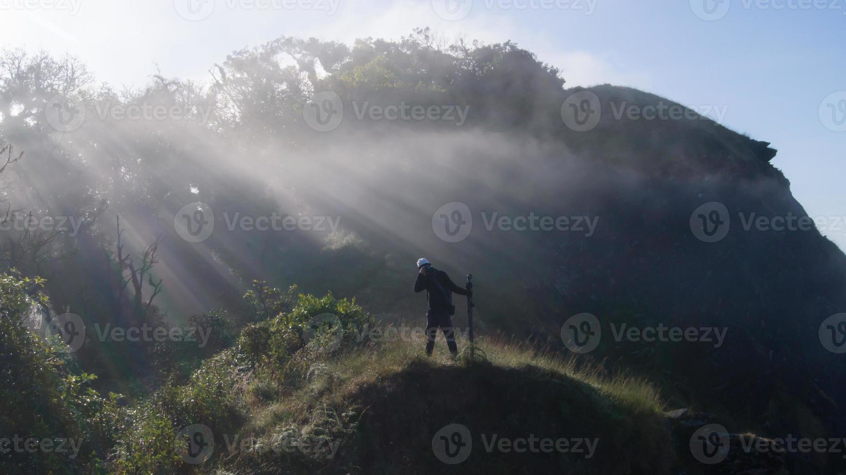 fotograaf die foto bovenop berg neemt