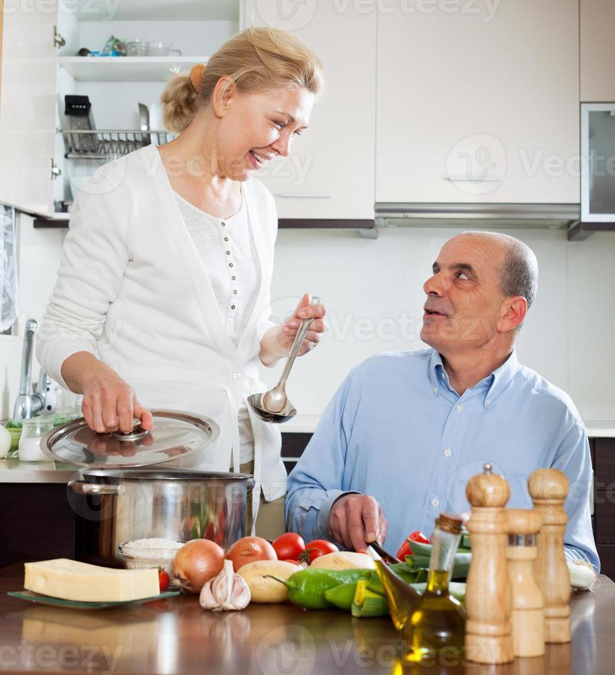 liefdevolle oudere senior en volwassen vrouw samen koken foto