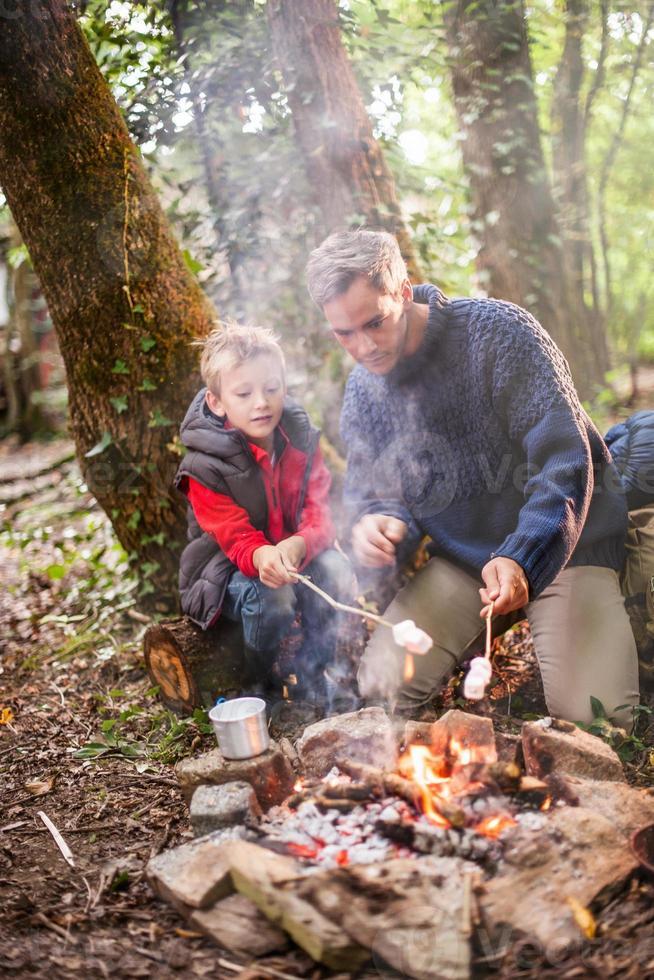 vader en zoon roosteren marshmallows op een kampvuur foto