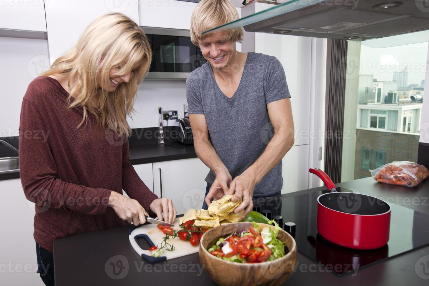 glimlachend Kaukasisch paar dat samen in keuken kookt foto
