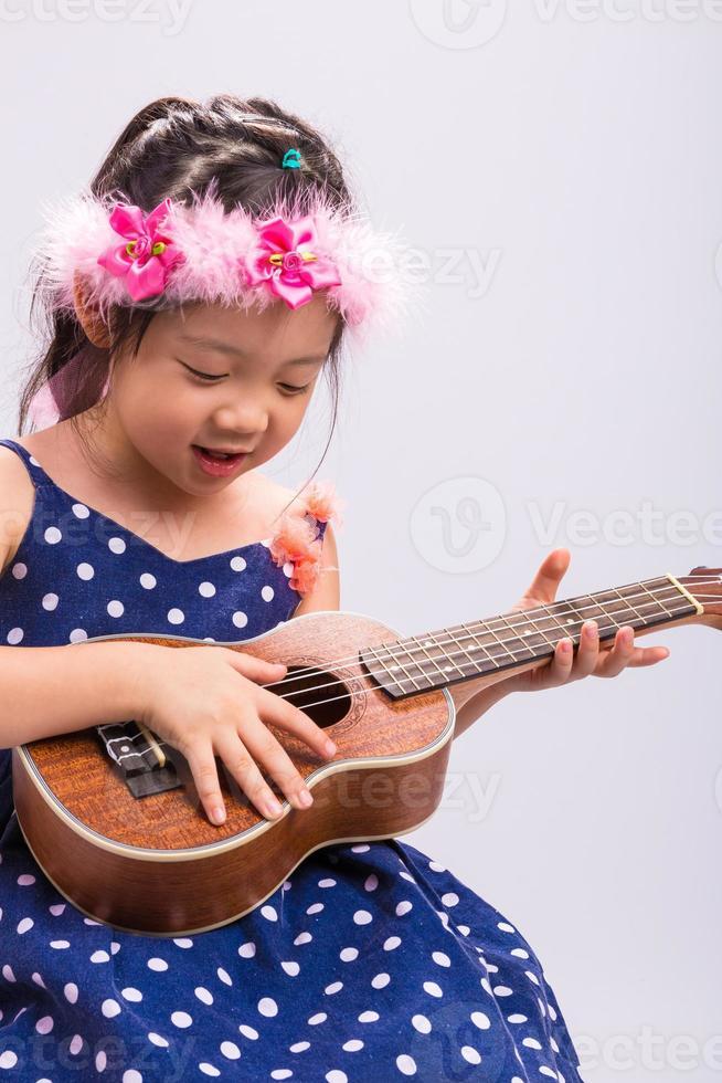 kind spelen ukelele / kind spelen ukelele achtergrond foto