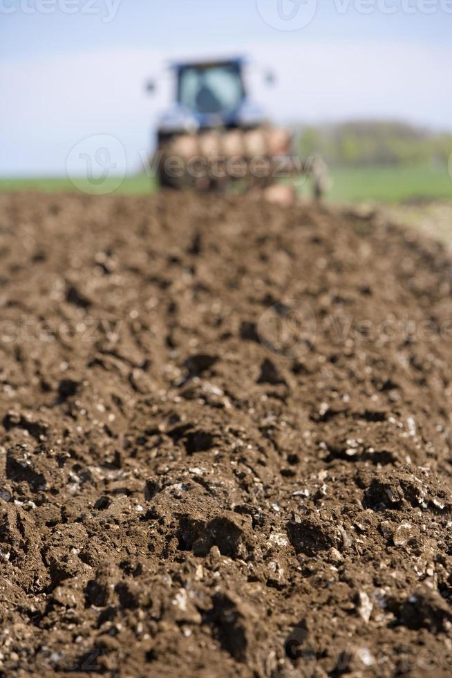 close up van geploegd veld met tractor en ploeg foto