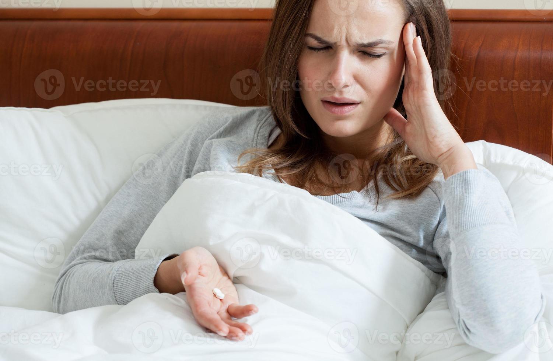 vrouw die pijnstillers neemt foto