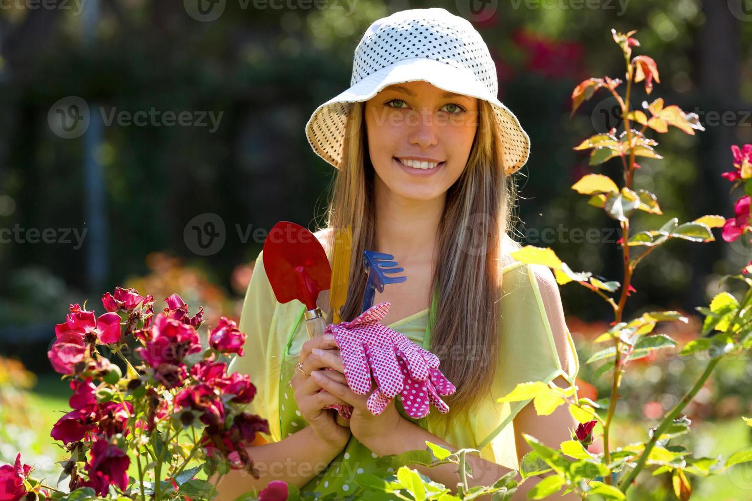 glimlachende vrouwelijke bloemisten in schort werken foto