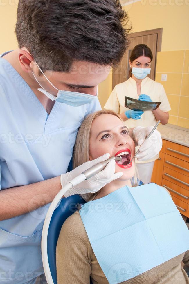 mannelijke tandarts en vrouwelijke assistent werken foto