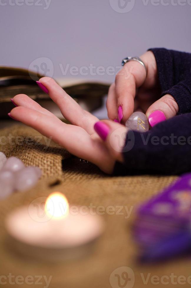 vrouwelijke hand met een magische runensteen foto