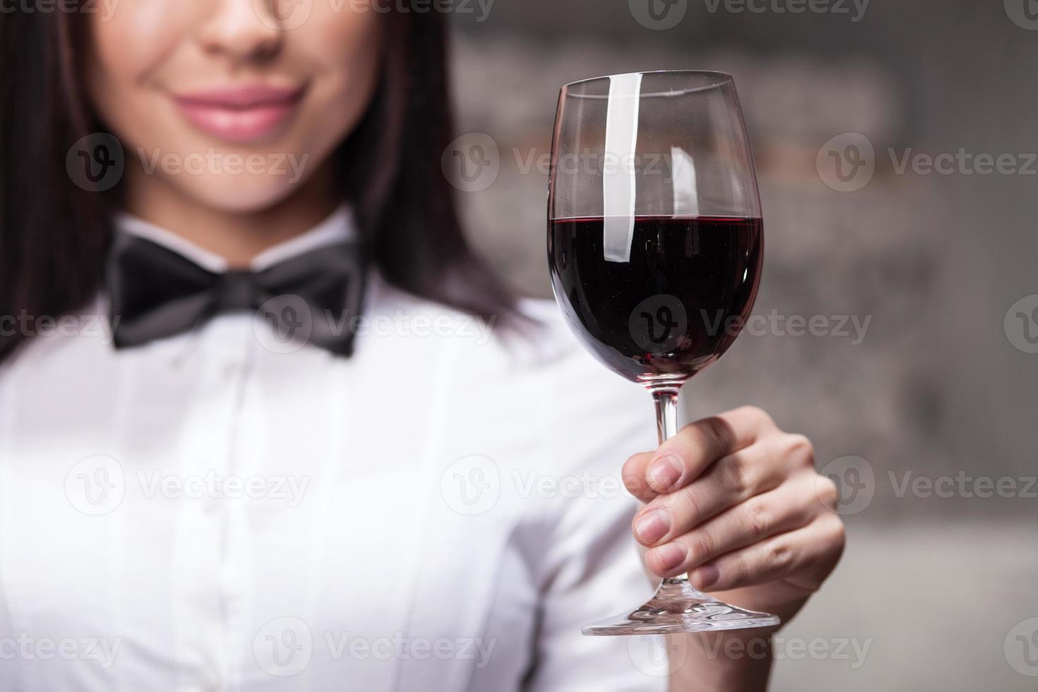 vrolijke vrouwelijke slijterij assistent met wijnglas foto