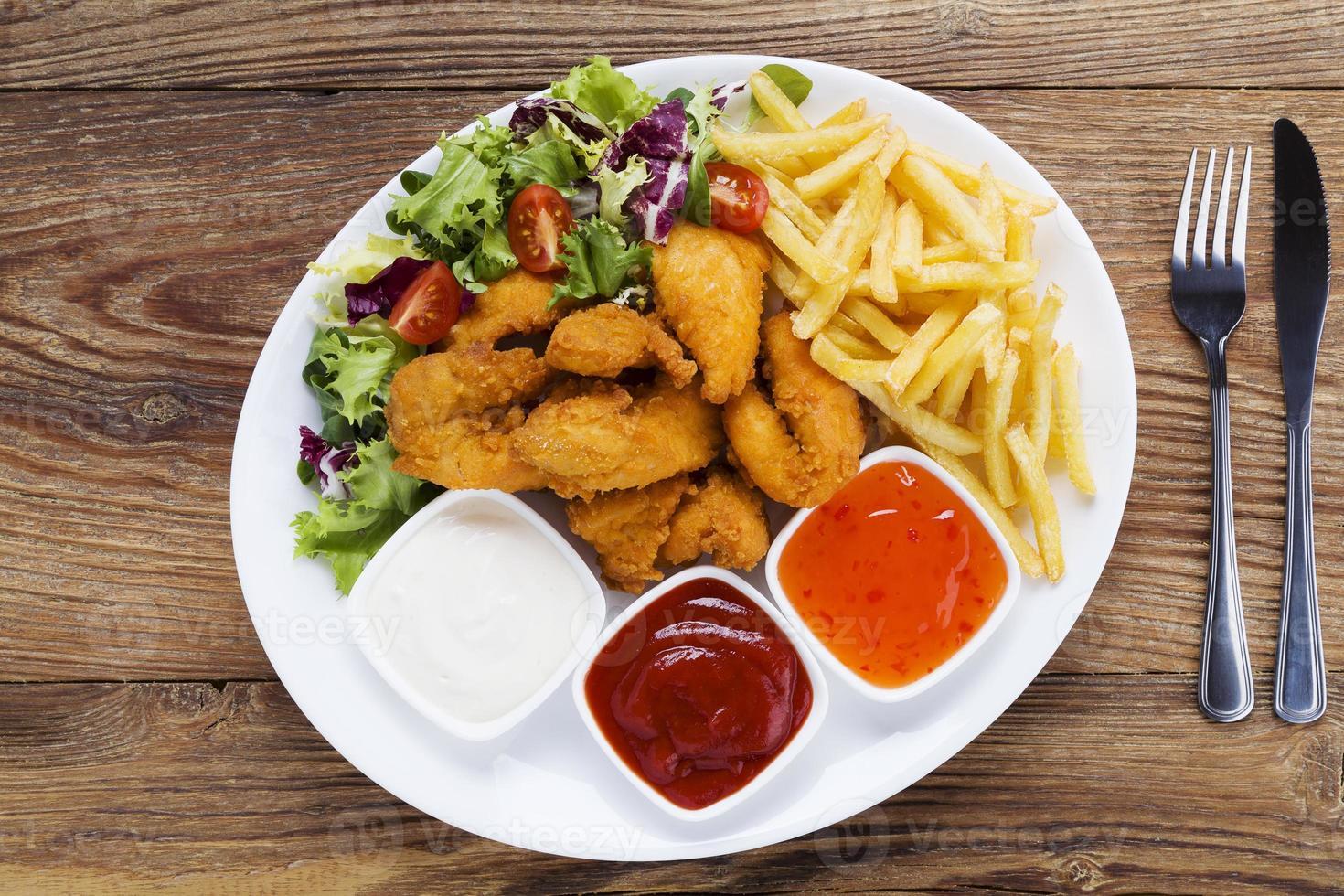 nuggets en chips geserveerd met dip en salades foto