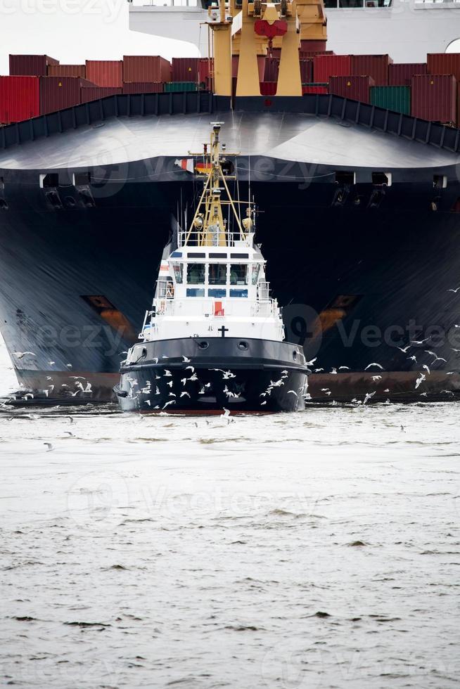 sleepboot trekken vrachtschip foto