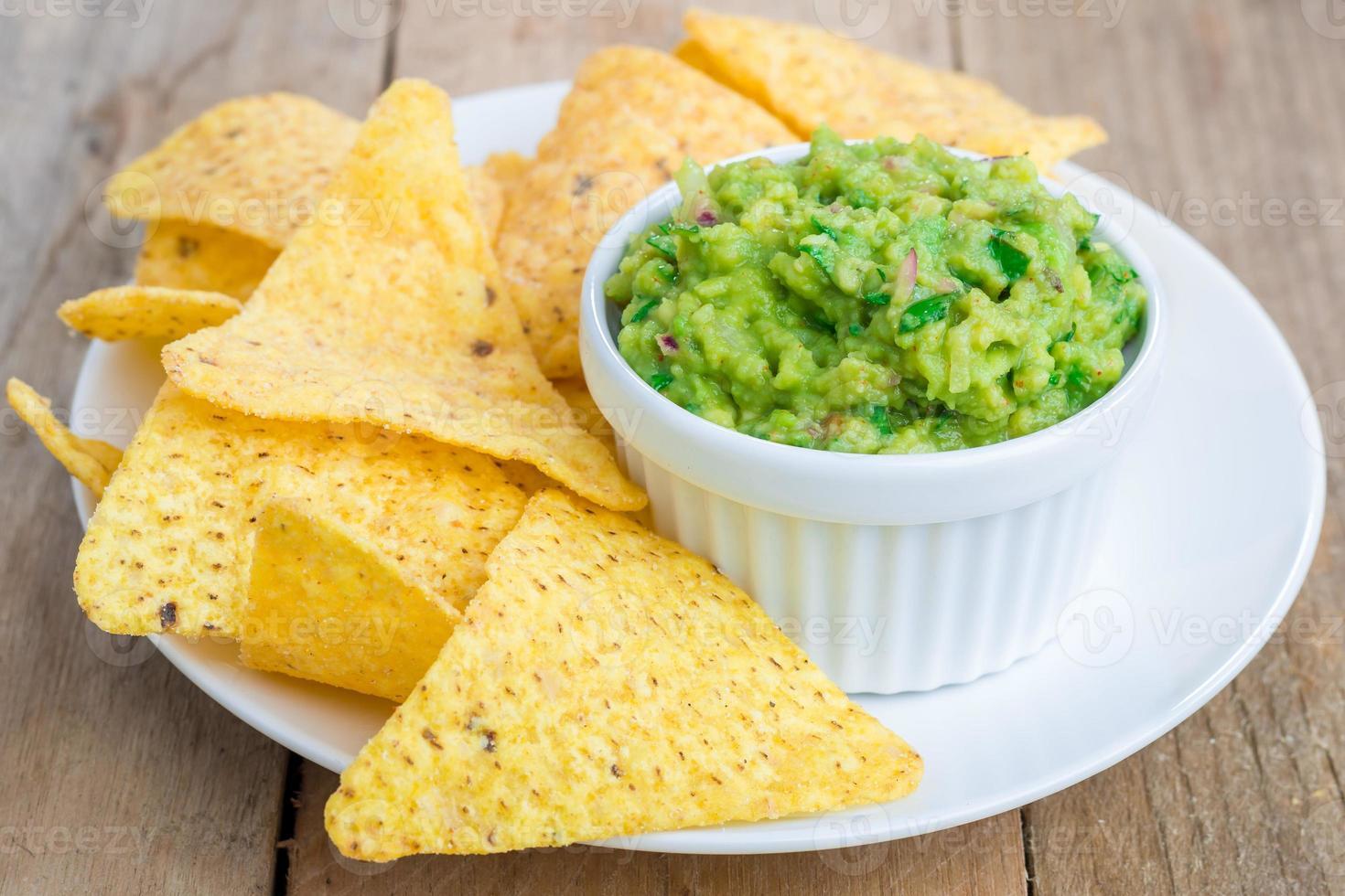 beker met dikke guacamole geserveerd met nacho's foto